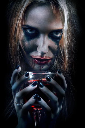 smeared: blond witch with bloody glass on black background, toned image