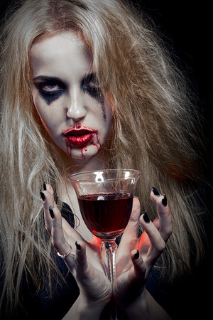 toned image: blond witch with bloody glass on black background, toned image