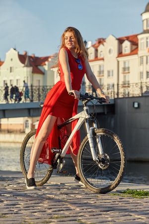 old biker: luxury woman on bike posing in old town