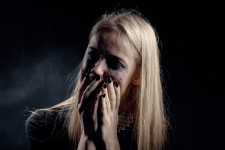 smeared: woman with smeared cosmetics crying on black background, monochrome