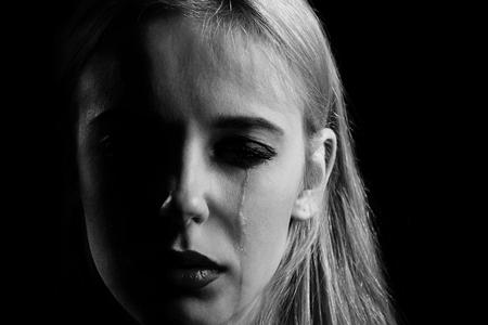 sad girl crying on black background, monochrome Stock Photo