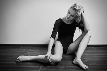 beautiful sad: sad girl sitting on wooden floor, monochrome Stock Photo