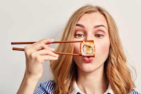 fun young woman eating sushi on black background