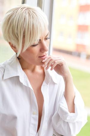 the thinker: sad woman thinker near window