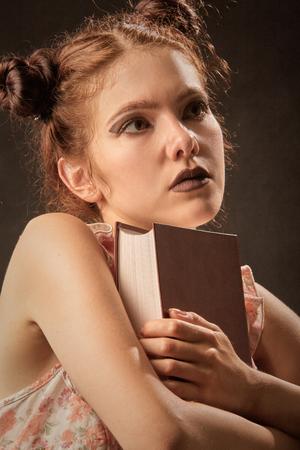 pensador: ni�a pensativa con pensador libro sobre fondo negro, imagen de tonos Foto de archivo