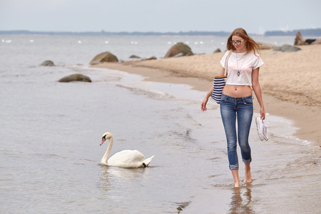 swimming swan: woman walking at sea beach with swimming swan