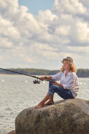 femme pêcheur assis sur le rocher à la plage de la mer