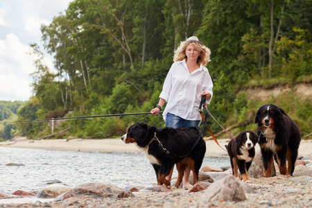 woman with her dogs on sea beach walking