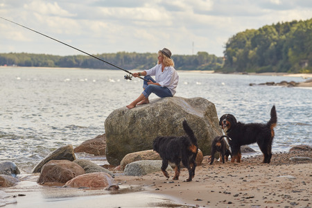woman fisher sitting on beach with dogs