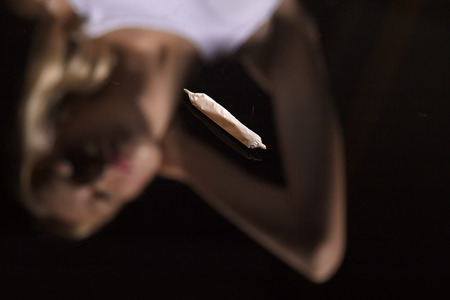 relaxant: joint with marijuana on black mirror background with female blurred reflection