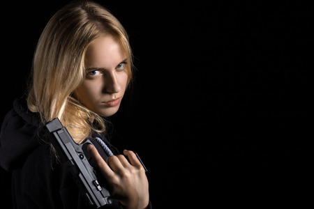 youth crime: beautiful girl with gun on black background with copyspace