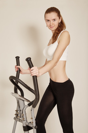 home trainer: slim beautiful woman exercising on home elliptical trainer