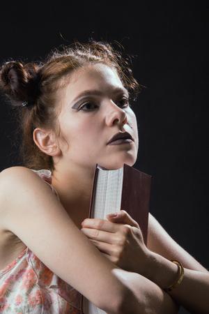 pensador: niña pensativa con pensador libro sobre fondo negro, imagen de tonos Foto de archivo
