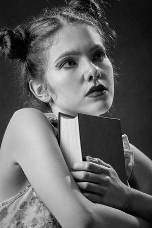 pensador: niña pensativa con pensador libro sobre fondo negro, blanco y negro Foto de archivo