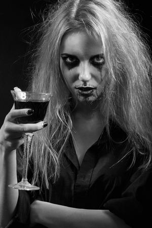 blond witch with bloody glass on black background, monochrome image Stock Photo