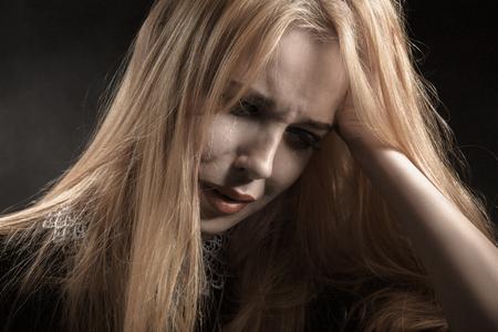 sad blond woman crying on black background