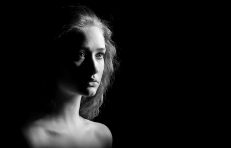 bared: sad girl with bared shoulders looks in camera on black background, monochrome image