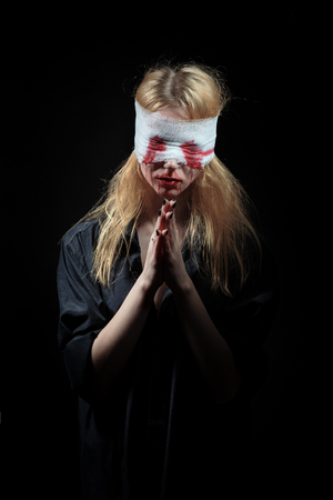 sad blooded woman on black background praying Stock Photo
