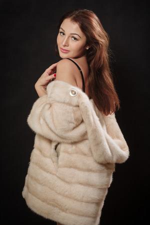 girl in fur coat undressing on black background