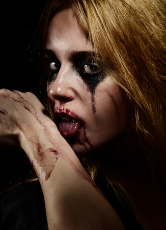 smeared: crazy blooded girl with smeared cosmetics licking blood