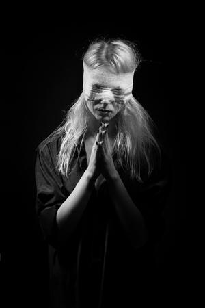 sad blooded woman on black background praying, monochrome