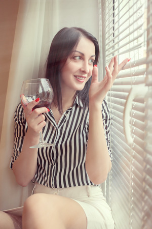 happy woman with wineglass looking through blinds