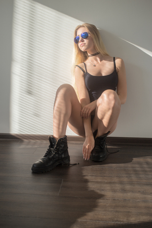 sensual blond girl in male boots sitting in sunlight on wall