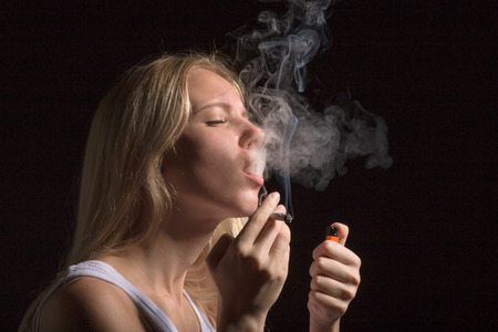blond young woman smoking on black background Stockfoto