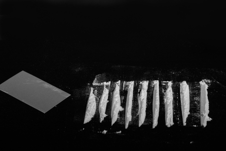 cutted: white cutted drug dust with credit card on black background with copyspace, monochrome