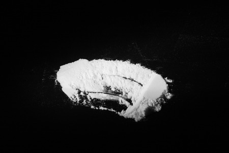 meth: white narcotic dust on black background, monochrome Stock Photo