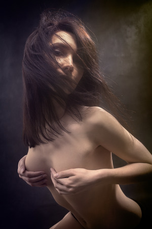 slim pretty naked girl cover her beautiful bared breast on black background