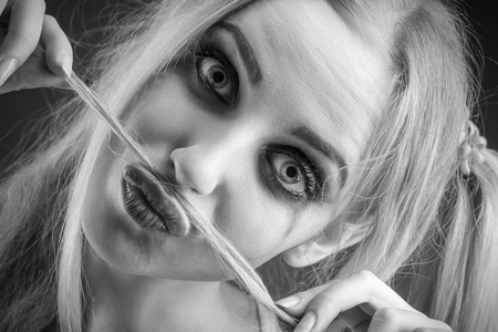 smeared: fun blond girl making fake mustache from her hair, monochrome image