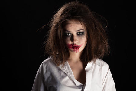pretty witch with fluffy hair and smeared cosmetics on black background Stock Photo