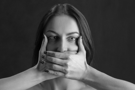 woman cover her mouth on black background monochrome
