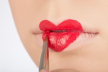 beautify: making heart symbol on female lips with brush