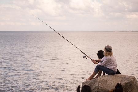 femme pêcheur assis sur la plage avec des chiens