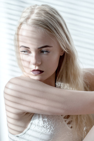 jalousie: sad girl sits in sunlight with blinds Stock Photo