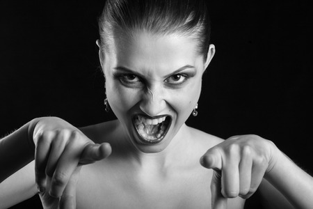 confrontational: angry beautiful woman point at camera screaming, monochrome