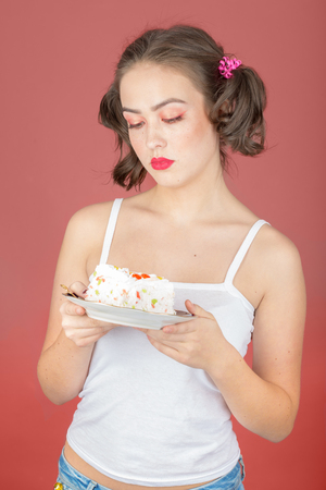 sad pensive girl with sweet dessert on red background