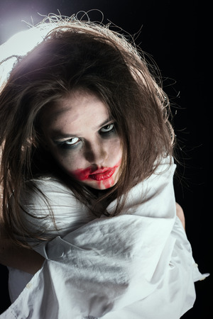 screaming crazy woman with fluffy hair in straitjacket on black background looking at camera