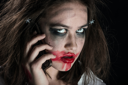 pretty fun crazy girl with fluffy hair, smeared cosmetics and telephone on black background looking at camera