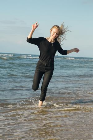 mulher feliz pulando na água na praia ensolarada do mar
