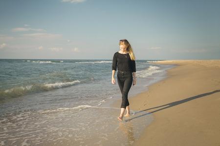 Traurige blonde barfüßigfrau, die am sonnigen Seestrand geht Standard-Bild - 83546842