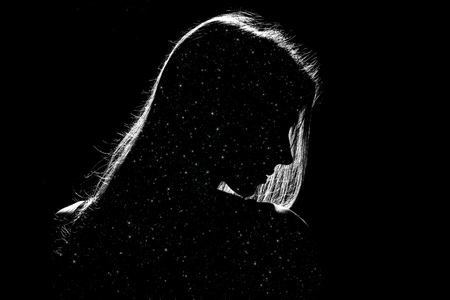 sad woman profile silhouette in dark with stars inside, monochrome image