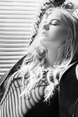 sensual aroused girl sitting on window in sunlight with blinds, monochrome