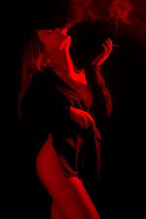 sensual woman in red lights on black background smoking