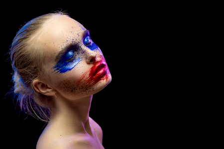 smeared mascara: female portrait with creative multicolored makeup on black background