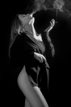 sensual woman on black background smoking and undressing