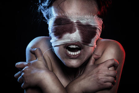 screaming crazy wounded bloody woman on black background Stock fotó
