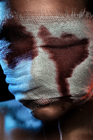 terrified woman: wounded bloody female head on black background